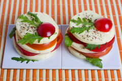 Appetizer. A light snack of cheese, tomato, and rocket salad Royalty Free Stock Image