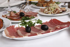 Appetizer. Mediterranic ham - on white restaurant table royalty free stock images