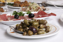 Appetizer. Olives - on white restaurant table royalty free stock image