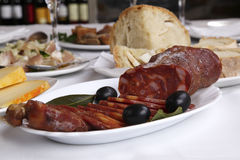 Appetizer. On white restaurant table - traditional mediterranic smoked sausage stock photography