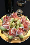 Appetizer. Prosciutto ham, Cantaloupe melon and red wine Royalty Free Stock Images