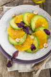 Appetizer of avocado, orange with purple basil and hazelnuts Stock Photos