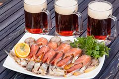 Appetizer for beer from dried fish, cheese sticks, smoked onion cheese and loafs with beer on the table royalty free stock photo