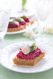 Appetizer with beetroot pesto and slice of herring on festive table Royalty Free Stock Photography