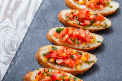 Appetizer bruschetta with chopped vegetables on ciabatta bread on stone slate background close up. Stock Photo