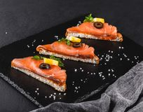 Appetizer bruschetta with fillet salmon, olives and lemon on ciabatta bread on stone slate background. Healthy food concept.  stock image