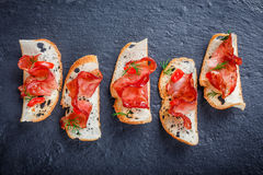 Appetizer bruschetta with jerky prosciutto on thinly sliced ciabatta bread on stone slate background close up. Royalty Free Stock Images