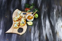 Appetizer bruschetta with pear, honey, walnut and cottage cheese on light wood board. Flat, top view, overhead royalty free stock photo