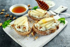 Appetizer bruschetta with pear, honey, walnut and cottage cheese on white board. Royalty Free Stock Image