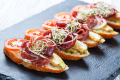 Appetizer bruschetta with prosciutto, tomato, zucchini on ciabatta bread on stone slate background close up. Stock Photo