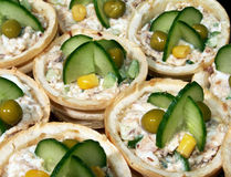 Appetizer canape. Group of snack tartelettes filled by fish salad with grated cheese, mayonnaise  and garlic. Tartelettes are decorated with pickled peas Stock Photography