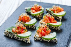 Appetizer canape with chopped vegetables and sesame on stone slate background close up. Stock Photo