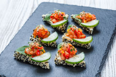 Appetizer canape with chopped vegetables and sesame on stone slate background close up Stock Photos