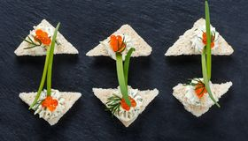 Appetizer canape with red caviar and cream cheese on stone slate background close up. Delicious snacks, sandwiches, crostini, brushetta, antipasti on party or stock photo