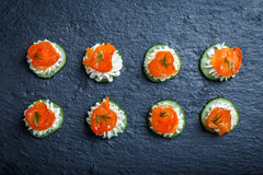 Appetizer canape with salmon, cucumber and cream cheese on stone slate background close up. Delicious snacks, sandwiches, crostini, brushetta, antipasti on stock photography