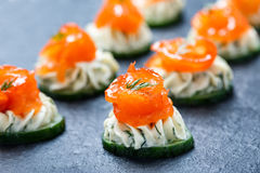 Appetizer canape with salmon, cucumber and cream cheese on stone slate background close up. Royalty Free Stock Photo