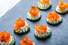 Appetizer canape with salmon, cucumber and cream cheese on stone slate background close up Royalty Free Stock Images