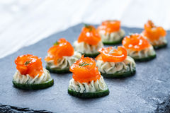 Appetizer canape with salmon, cucumber and cream cheese on stone slate background close up. Stock Photo