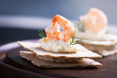 Appetizer canape with shrimp, cheese and dill on a small loaf of bread Stock Image