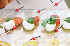Appetizer, Caprese. Cherry tomatoes,mozzarella and Basil on skewers. . Pesto sauce. Tasty buffet table. Summer party stock photography