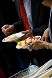 Appetizer during a catered party or event. Small plates being held by guests during a party. This image has a very shallow depth of field Stock Photos