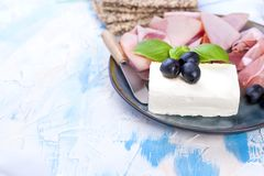 Appetizer of cheese and ham on a blue plate and light background. Free space for text or advertising stock photography