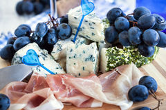 Appetizer with cheese, ham and grape stock image