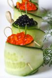 Appetizer of cucumber rolls with red and black caviar Stock Photos
