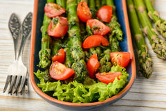 Appetizer - delicious vegetarian salad with green asparagus, tomatoes and vinaigrette dressing. Royalty Free Stock Photos