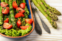 Appetizer - delicious vegetarian salad with green asparagus, tomatoes and vinaigrette dressing. Royalty Free Stock Photography