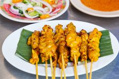 Appetizer dish of traditional Thai street food recipe, Pork Satay Grilled pork stick putting on banana leaf in white plate served stock photo