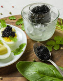 Appetizer of eggs, white sauce and black caviar. Layout on a wooden background with spices and herbs. Stock Photography