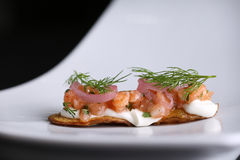 Appetizer on fried potato skins of red salted salmon, cream cheese, onions and dill at white plate. Closeup Royalty Free Stock Images
