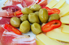 Appetizer. Green olives with sliced prosciutto, smoked goat cheese and a few pieces of red, hot pepers served on rustic, ceramic plate Royalty Free Stock Image
