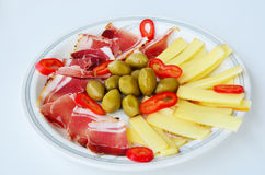 Appetizer. Green olives with sliced prosciutto, smoked goat cheese and a few pieces of red, hot peppers served on rustic, ceramic plate Stock Photography