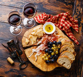 Appetizer ham and cheese plate with wine. On wooden table background royalty free stock image