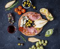 Appetizer, italian antipasto, ham, olives, cheese, bread, grapes, pear and glass of wine on dark stone background. Stock Photos