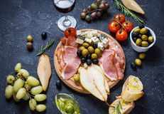 Appetizer, italian antipasto, ham, olives, cheese, bread, grapes, pear and glass of wine on stone background Stock Images
