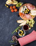 Appetizer, italian antipasto, ham, olives, cheese, bread, grapes, pear and wine on dark stone background. Top view Royalty Free Stock Images