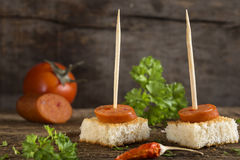 Appetizer made with paprika frankfurter sausage. With herbs on wooden background Stock Images