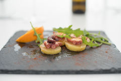 Appetizer of octopus with potatoes and arugula on black plate. Typical Spanish appetizer of octopus with potatoes and arugula on black plate, tapas Stock Images