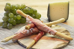 Appetizer with Parma ham on breadstick Stock Photos