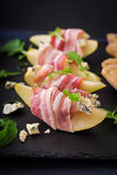 Appetizer with pear, blue cheese, prosciutto ham and toast. For holidays on a dark plate Royalty Free Stock Photos