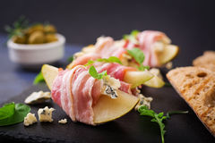 Appetizer with pear, blue cheese, prosciutto ham and toast for holidays. On a dark plate Royalty Free Stock Images