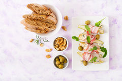 Appetizer with pear, blue cheese, prosciutto ham and toast for holidays. On a white plate. Flat lay. Top view Stock Photos