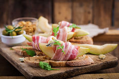 Appetizer with pear, prosciutto, ham, blue cheese for holidays and toast. On wooden background Royalty Free Stock Photography
