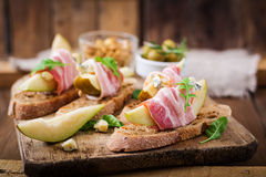 Appetizer with pear, prosciutto, ham, blue cheese for holidays and toast. On wooden background Stock Images