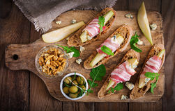 Appetizer with pear, prosciutto, ham, blue cheese for holidays and toast. On wooden background. Flat lay. Top view Royalty Free Stock Photography