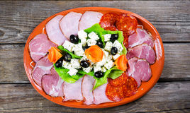 Appetizer on the plate and the old table Royalty Free Stock Photo