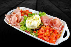 Appetizer plate with prosciutto crudo, chopped tomatoes, salad and burrata. royalty free stock photos